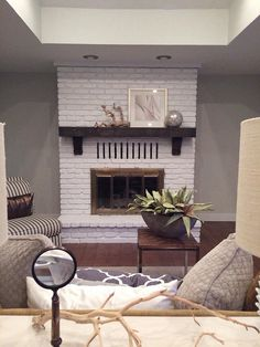 Painted brick fireplace  wood mantle and brass gate