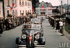 Hitler and his accompanying convoy of Mercedes-Benz sedans greet the enthusiastic masses en route to give a speech to the German people.