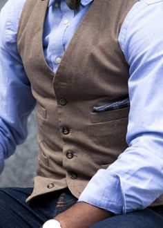 Brown undercoat with baby blue shirt, bow tie, and dark denim pants.