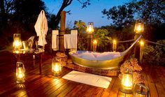 """Sanctuary Baines' Camp, a five-suite retreat located on a private concession bordering the Moremi Game Reserve. The """"star bath"""" is a free-standing bathtub on the candlelit suite deck with views of the shimmering Boro River."""