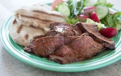 """London broil,"" often call top round, is the perfect cut for easy summertime entertaining. A tangy marinade of lemons and garlic ensures this cut is tender and juicy. Serve with a big green salad and a pile of warm pita bread."