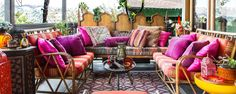 Boho patio/balcony. So many gorgeous colors and textiles!