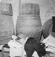 A woman sleeps on a bed made on top of a row of barrels in the cellar of a wine merchant's in East London in 1940.