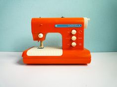 """Vintage pretty sewing machine toy in beautiful orange color.  Comes from the 70s/80s, its name is """"Gabriela"""" and was produced by PIKO in Germany (DDR)."""