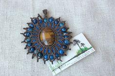 Colgante de macramé con hilo encerado marrón y azul . Tiene una piedra semipreciosa central de ojo de tigre y bolas de ágata azul.