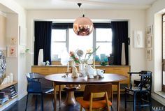 A Tom Dixon copper-shade pendant lamp hangs over the teak table in DeWoody's sunny dining room.