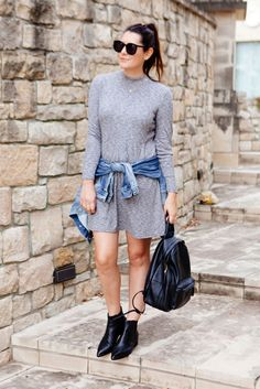 The Best Outfit Ideas Of The Week: Fashion blogger 'Kendi Every Day' wearing a grey mock neck long sleeve knit dress, black pointy toe booties, a denim jacket tied around the waist, a black leather backpack and black sunglasses. Fall outfit, fall layers, comfy outfit, casual outfit, street style, street chic style, boho outfit, boho chic outfit, boho chic style.