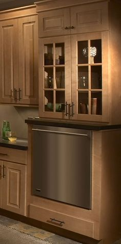 maple cabinets with glass front doors above raised dishwasher