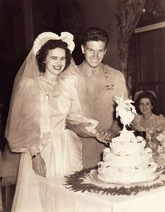 1940's military style wedding with smiles all around as this young couple slices into their wedding cake.