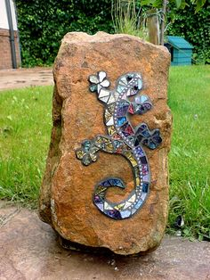 I probably wouldn't use a gecko, but another design might be nice - Greenman?  A Celtic knot?  A Celtic swirl?  There are many ways to personalize it.  Gecko on the Rock; glass on sandstone; by Gisela Gibbon, Scarborough, North Yorkshire.