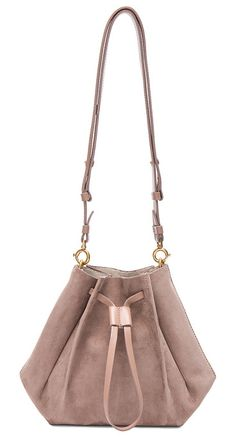 Bucket Bag by MAISON MARGIELA. Nubuck leather with raw lining and brushed gold-tone hardware. Made in Italy. Measures approx 8W x 8.5H x 5.5D. Adjustable and detachable leather shoulder strap. Drawstring opening. Snap button closures along bottom. MMAR-WY54. SY0760. A... #maisonmargiela #bags