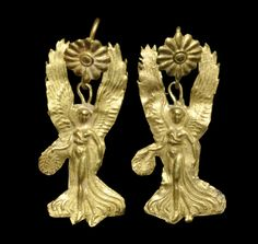 4th-1st century BC. A pair of Hellenistic sheet-gold bifacial earrings depicting the goddess Nike (Victory) advancing with a wreath of laurel leaves in her right hand.