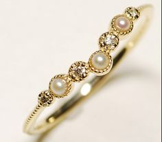 $340  Beautifully delicate half eternity ring with real pearls and diamonds. Made by hand with a unique band with highly detailed texture Metal: 10k Gold  Gem: Fresh Water Pearls & Natural Diamonds  Width of ring: 1.1mm  Production Time: 2- 3 weeks ( all our items are custom made ) Shipping: 10-15 days worldwide  Custom designs and special orders are welcome! ❥ All orders will be shipped in a nice jewelry box