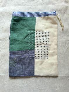 エメラルドグリーン、2色のブルーとホワイトのリネンをパッチワークし白とブルーと黄緑の糸でちくちくした巾着です。