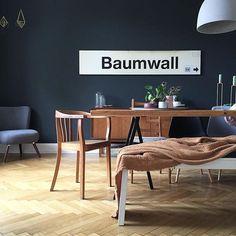 """Esszimmer - Schwarze Wand mit """"Baumwall""""-Bahnstationsschild, dazu passendes Braun, Tisch aus alten Dielen, Fischgrätenparkett, die Kommode ist ein Erbstück von der Oma"""