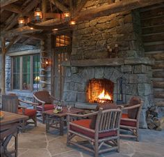 Incredibly rustic outdoor porch with a beautiful large fireplace in this log cabin.