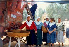 Women of Turri, gather around the harvesting machine.