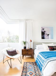 Bright boho-inspired bedroom with a gray linen headboard, Aztec printed runner, and a wooden chair