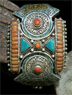 This Old Tibetan Bracelet was handcrafted in the early 1900's. It is an usual piece of antique articulated jewelry that almost comes to life as moves with the wrist to maintain its fit and expose decorated edges. Like Classic Tibetan Tribal Jewelry, this bracelet is ornately decorated on all sides in Turquoise, Coral, Silver and Brass.