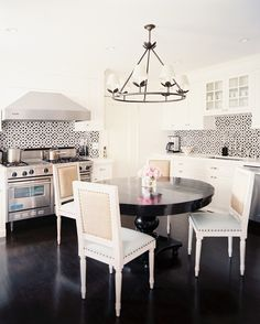 White kitchen and dining space with tiled backsplash
