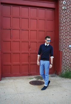 Shop this look on Lookastic: https://lookastic.co.uk/men/looks/crew-neck-sweater-long-sleeve-shirt-jeans-derby-shoes-tie-belt-sunglasses-socks/4000   — Blue Sunglasses  — Navy and White Polka Dot Tie  — Navy Crew-neck Sweater  — White Long Sleeve Shirt  — Dark Brown Leather Belt  — Light Blue Lightweight Jeans  — Navy and White Horizontal Striped Socks  — Navy Suede Derby Shoes