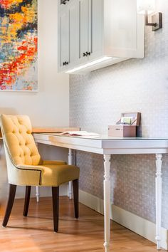 For the other workspace, designer Harmony Weihs created a custom desk using reclaimed stair spindles. An upholstered chair and glitzy wallpaper add a feminine touch.