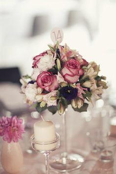 Table numbers in flowers... is that a martini glass for a vase?