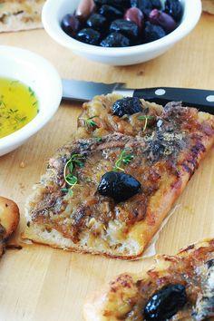 La pissaladière, une recette niçoise avec une pâte à pain ou à pizza, oignons confits et ail, anchois et olives, des herbes aromatiques. Un régal pour les amateurs d'oignons et d'anchois. Dégustez-la chaude ou froide. Avec une petite salade, cela vous fait un bon plat complet. Hors D'oeuvres, Pie Cake, Yummy Cupcakes, French Food, Vegetable Pizza, Sausage, Picnic, Sandwiches, Bbq