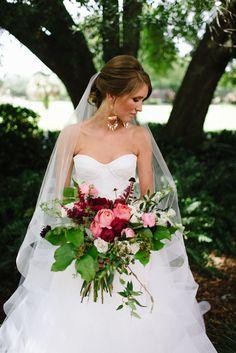 bride's lush, loose and wild summer bouquet of pink romantic antique garden roses, red charm peonies, burgundy astilbe, burgundy scabiosa, pink ranunculus,white majolica spray roses, white larkspur, fern, jasmine vine, lemon leaf. crepe myrtle and seeded eucalyptus.