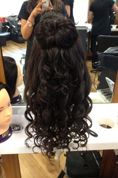 A big bow and curls for a girly half up half down hairstyle.