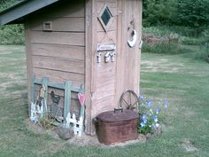 an old outhouse that was once used now makes a fun centerpiece for a country look