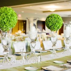 Modern Pomander Centerpieces    Having enough room for a banquet-sized dining table in the center of the room was one of the things that sold the couple on their venue. They topped it with a mix of vases, candles and pomanders for a minimalist, mod look.