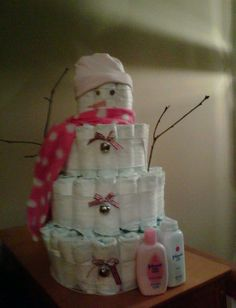 Snow Woman Diaper Cake. I made this for @Angela Holland's baby shower.  I can't take full credit for the idea.  I got that from lilbabycakes.com.  I did try to mimic their's as much as possible.  I did fix the slanted diapers at the bottom before giving it to mommy by the way.  Also, I suggest using brown pipe cleaners for the arms instead of sticks like I used.