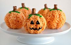 Jack O'Lantern Treats | These adorable Jack O'lantern rice krispie treats are a no bake sweet that can be made in a flash.  Rice cereal is combined with butter, melted marshmallows and food coloring to form the base of the pumpkins.  They are shaped using a mini bundt cake pan which gives them curves similar to those seen on a real pumpkin.  A tootsie roll stem and green icing leaves decorate the top while black icing is used to draw on the face. @FoodFamilyFinds