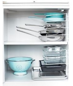 Stacking Pans  Turn a vertical bakeware organizer on its end to stack pots and pans instead of nesting them. Secure it to the cabinet wall with cable clips to prevent toppling. #Marthastewart