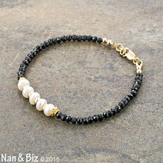 This delicate black spinel and white button pearl bracelet features five lustrous, high quality 6mm white pearls separated by four simple 14K