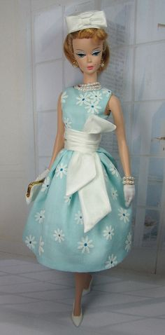 A pretty and feminine vintage style cut from and beautiful aqua daisy printed cotton, fully lined in china silk, and features scoop neck bodice, pleated skirt and button over snap back closure. A detachable ruched waistband and bow are off whtie china silk and close in back with loop and buttons The matching pillbox hat is fully lined and finished with a dressmakers bow.   SHOES,  JEWELRY, GLOVES,  SUNGLASSES, PURSE, STOCKINGS, DOLL AND DIORAMA NOT INCLUDED. Accessories are from  Mattel ...