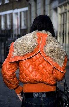 Quilted orange bomber jacket with a fur lined zip hood,