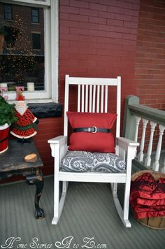 Christmas porch decor - I think my favorite part is the red pillow with the belt on it.  I would never have thought of that.