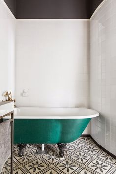 Decorative black and white tiles, white tiled walls and the most beautiful teal bathtub with black legs. I want this bathroom