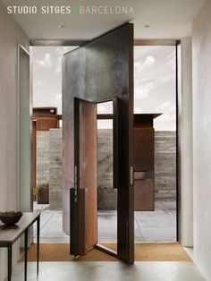 Revolving door - a tall steel pivot door is inset with a pilot door, allowing for varying degrees of openness between the indoor and outdoor spaces.