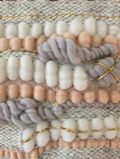 Handmade woven wall art in speckled grey wool yarn, light pink roving, light grey/purple roving, Ivory roving, blush cotton yarn, and gold ribbon. Hung