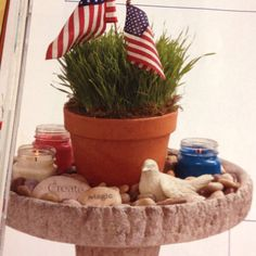 Great idea for using birdbaths for creative decorating from Country Sampler. Fill the basin of a birdbath with river rocks and decorative stones. Then, nestle a terra-cotta   pot of pet grass in the center and add red, white and blue candles and miniature flags for color.