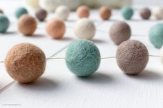 Precious Little Miracle - Felt ball garlands are great not only for nursery and home décor, but also for parties, showers, weddings, and special occasions and even if you think you have a plain wall to decorate! They are versatile, reusable and always add a whimsical and beautiful touch to any ambience, backgrounds and liven up that environment. Colours: Grey, Mint, Latte, Peach, Cream  Details: • Handmade with 100% wool felt balls of 2.5cm each (about 1 inch) • Strung on a strong cotton…
