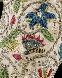 Detail of a lady's embroidered jacket from the Jacobean period. The jacket is covered with embroidered flowers, bees and birds, and includes gold and silver thread and spangles. C. 1600 - 1625