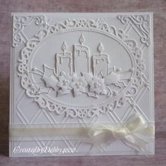 handcrafted Christmas card from A Scrapjourney .,. all white ... layers ... die  cuts ... embossing ... glitter and pearls ... trio of candles with punched poinsettia and holly ... lacy oval ... gorgeous card!!!
