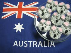 Koala/Lamington Cup Cakes Buttercream frosting coloured with black food colouring until it makes a silvery grey colour. Dip in coconut. Ears made from pink marshmallows, cut in half, iced and coated in coconut. Eyes are mini choc chips or mini chocolate M&M's, nose is a black jelly bean.