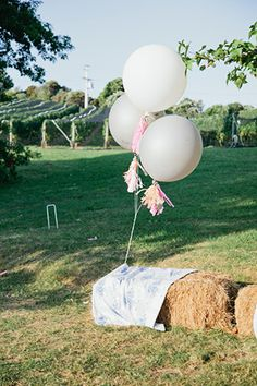 bales of hay with giant white balloons - perfect for fun outdoor wedding decor!  | so simple outside for a field wedding www.onefabday.com