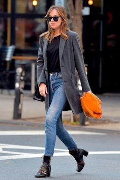 12 October Earlier in the day, Dakota Johnson was spotted in New York in a grey tailored coat, jeans and Gucci boots.