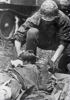 A Waffen SS soldier gives an injured Soviet infantryman a drink of water in the USSR during WW2 in 1943